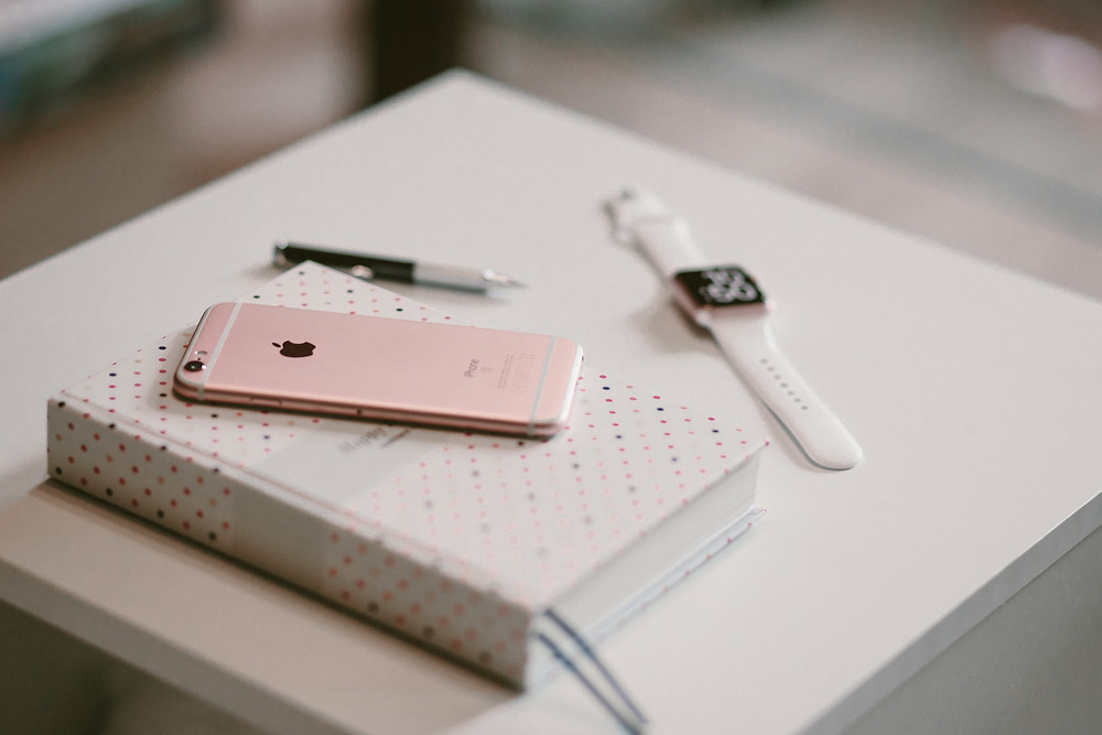 Journal, phone, pen, and an Apple Watch on a nightstand