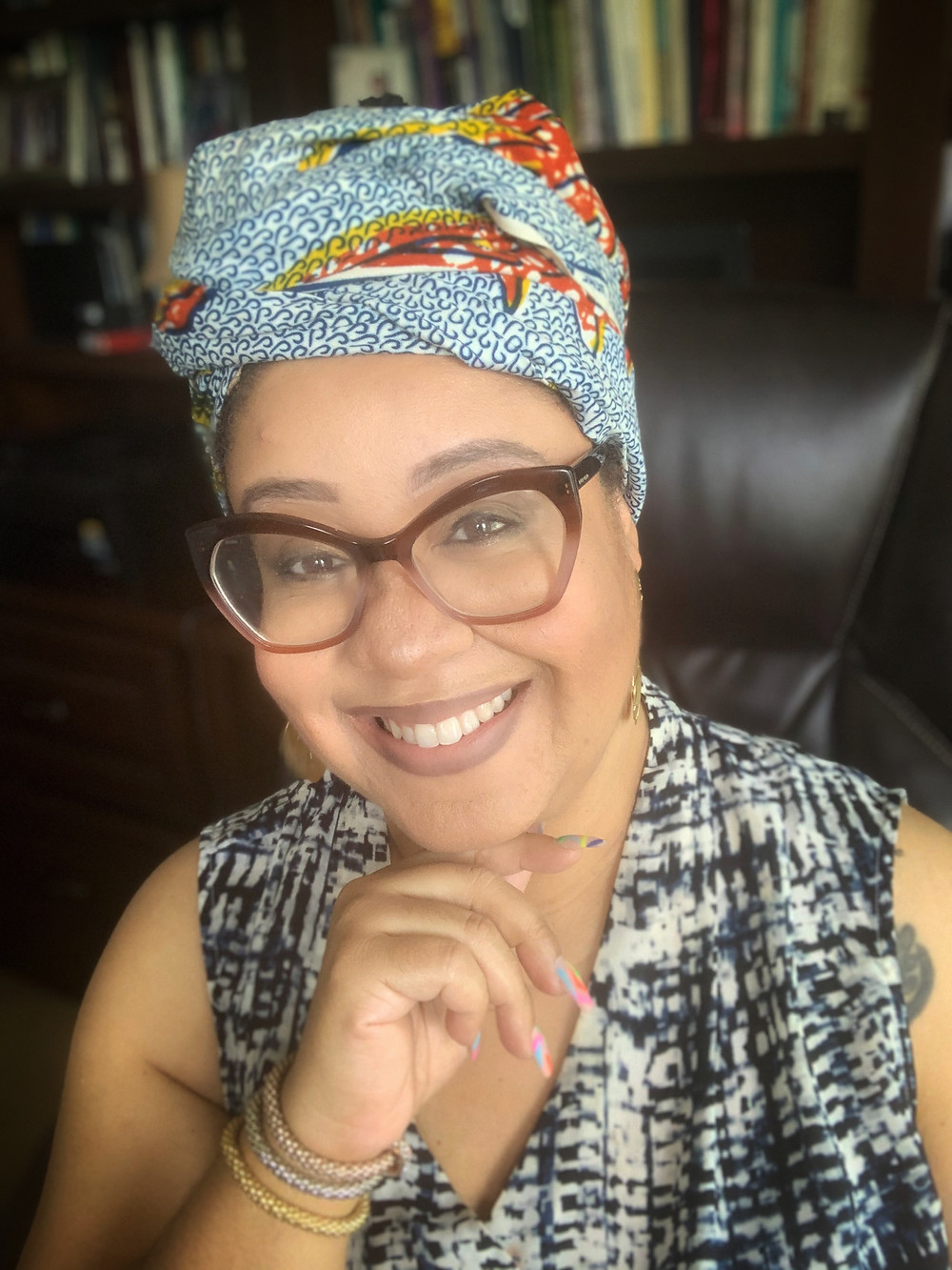 A black woman in a head wrap smiling at the camera.