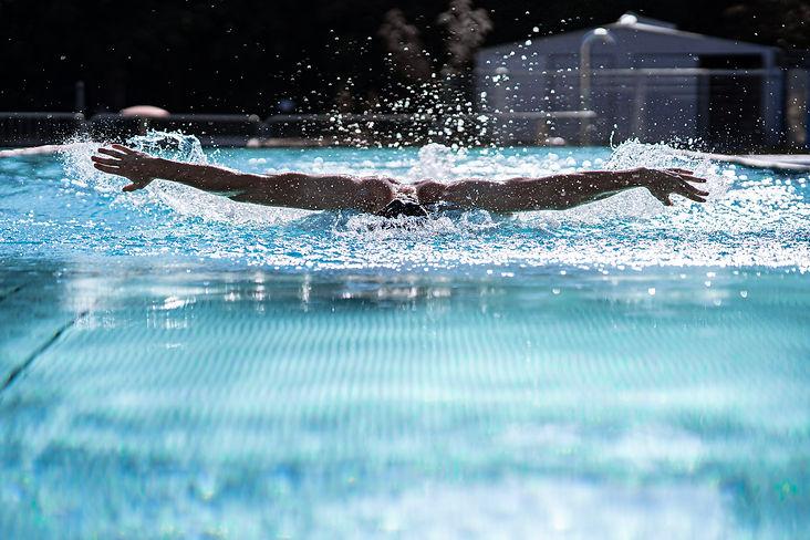 Delfinschwimmer in Frontansicht mit ausgebreiteten Armen