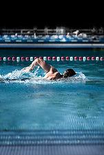 Muskulöser Kraulschwimmmer von der Seite mit hoem Ellebogen