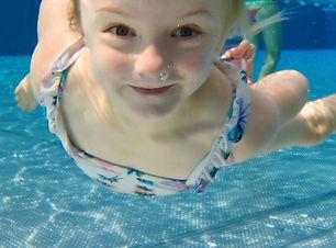 kleines Mädchen unter Wasse mit Blick in die Kamera