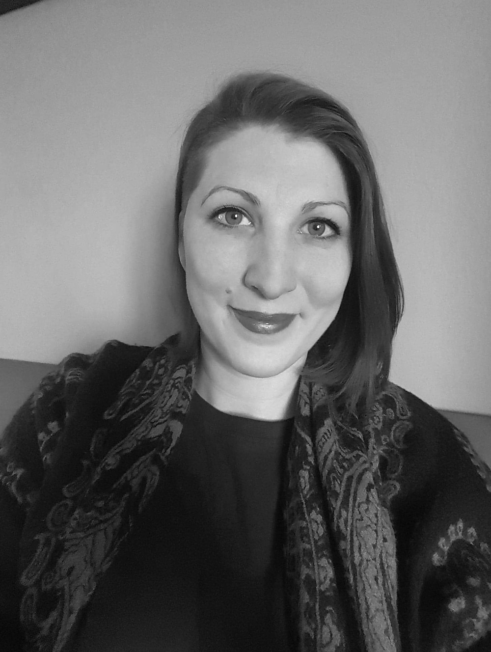 A black and white headshot of Sophie, a white non binary person in her early 30s. She's wearing bright lipstick, a soft patterned scarf around her shoulders and a dark jumper. She has a shoulder length bob with a side shave. She's smiling a tthe camera.