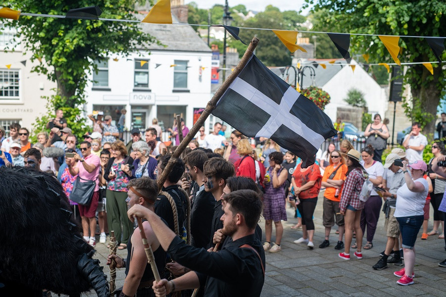 A colourful crowd gather on Bodmin's Mount Folly square during Bodming Riding Festival 2019. There is Cornish bunting in black and gold and the Helliers with the Beast of Bodmin are waving a Cornish flag.