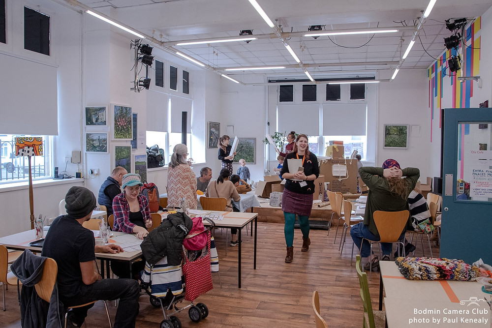 A colourful shot of a large, busy room at The Old Library, with a stage at the end where cardboard boxes are being made into buildings. There are all kids of people at tables on either side of the room and down the middle Sophie is walking towards the camera, holding a clipboard. She's wearing green tights, a purple skirt and a black and rainbow print jumper, with a bright orange intoBodmin lanyard, and is smiling.