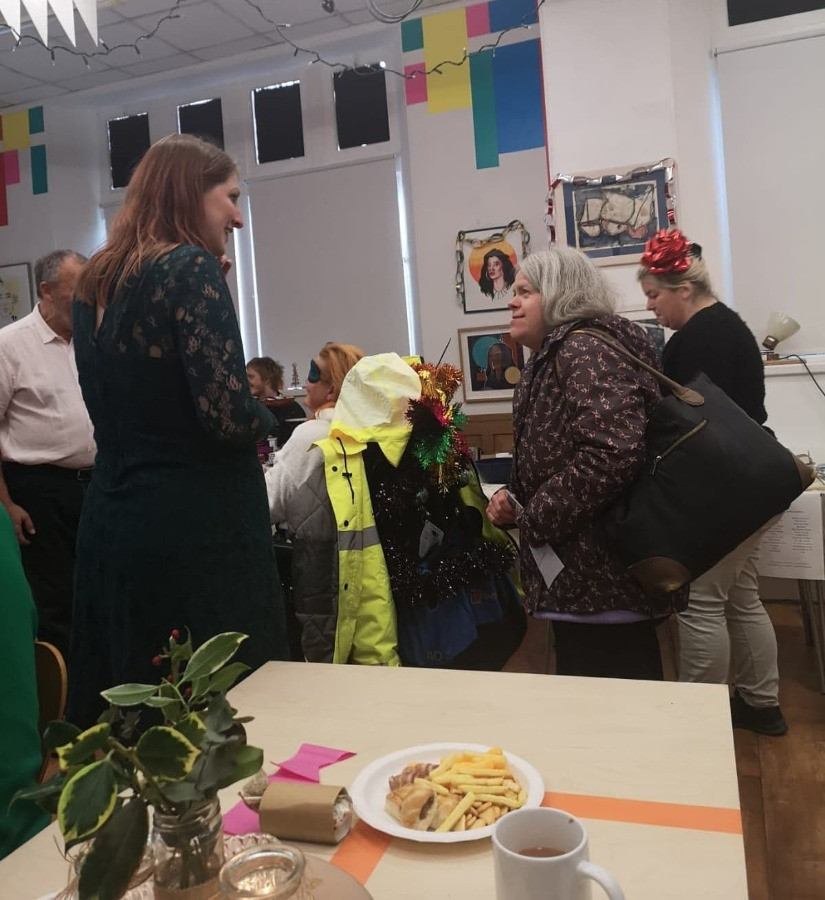 A shot of part of the large room at The Old Library. There's a table with a festive holly table decoration and plate of nibbles in the foreground, and a group of people behind, including Sophie in a green dress, talking to a shorter lady in a patterened jacket. One of the people in the background has tinsel in their hair, and another has tinsel on their wheelchair.
