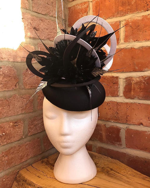 Black fabric button with silver loops and silver tipped feathers