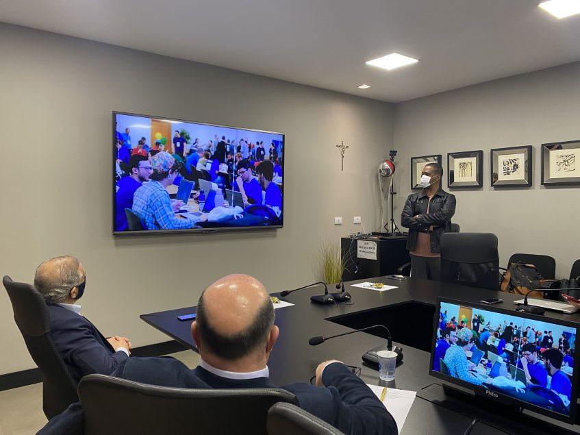 Presidente Ricardo, presidente Kita e, ao fundo, o geog. Jorge Campelo apresentando o evento.