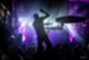 Artist singing on stage during concert with creative lighting.