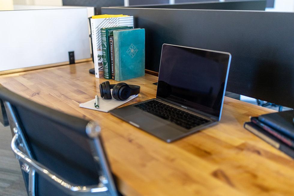 Desk wth computer, headphones, and books