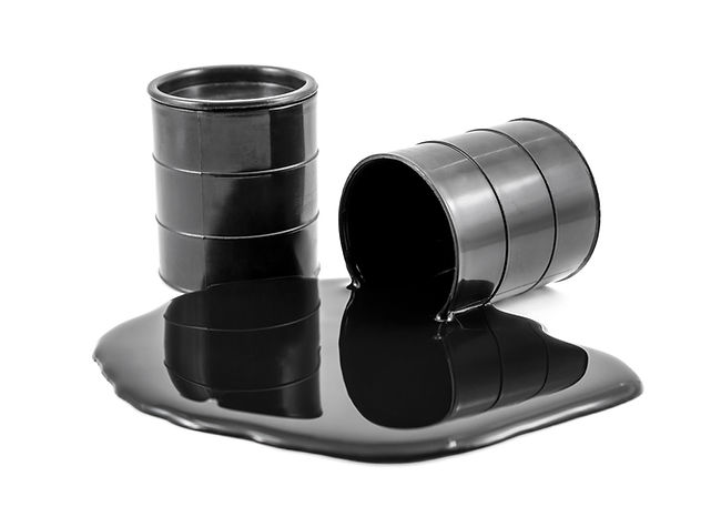 Oil is poured out of the black barrel an