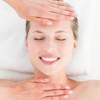 Calm woman receiving reiki treatment in