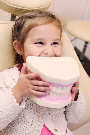 baby girl smiling sitting in dental chai
