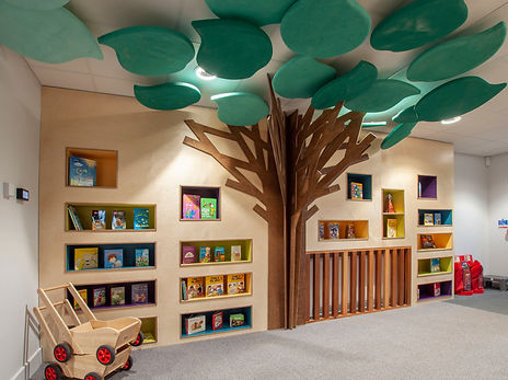 primary school library with feature tree and brightly coloured shelves