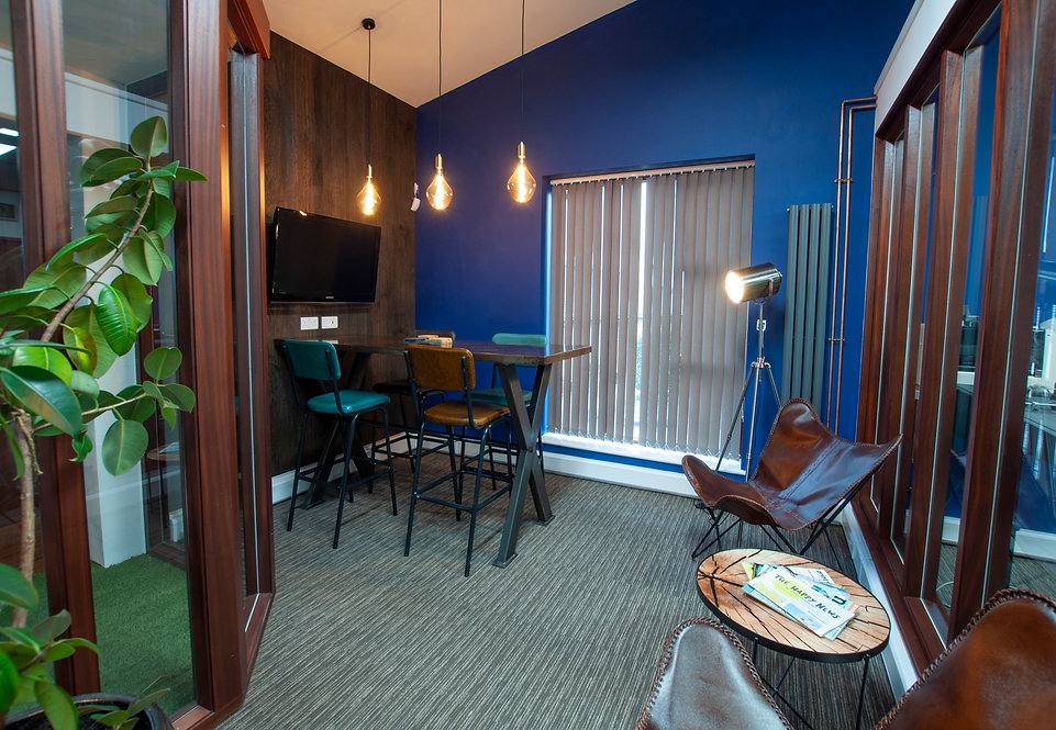 office breakout area with tv screen and leather lounge chairs