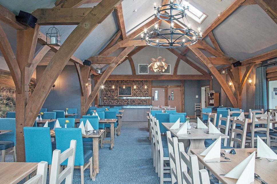 oak frame restaurant with bespoke carpet and Tom Raffield lighting