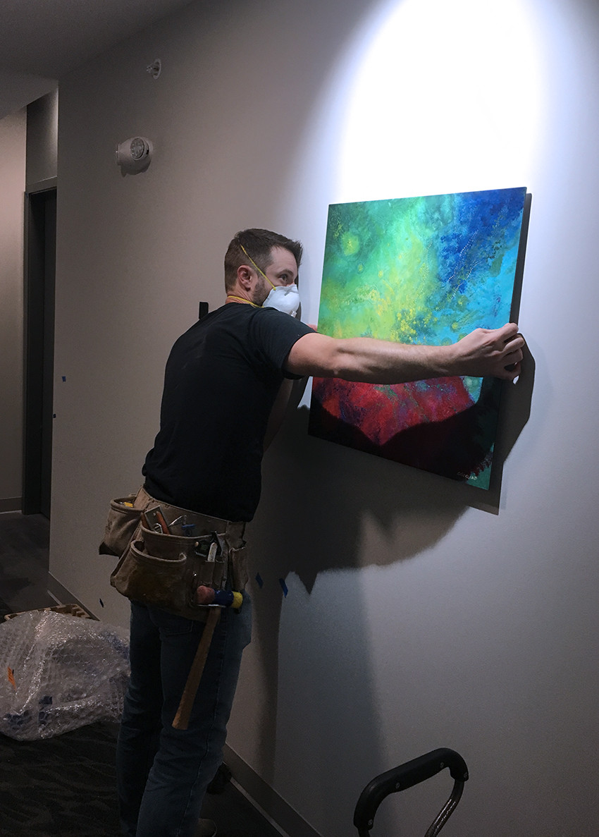 Shawn carefully adjusts the Cosmic Seas print during installation at The Lofts at City Center.