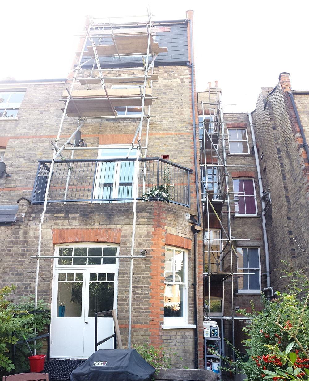 Painting exterior woodwork back of property Highgate, London, N6