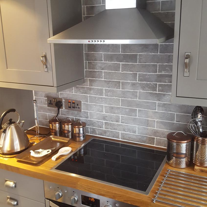 Grey splashback tiles, white grout