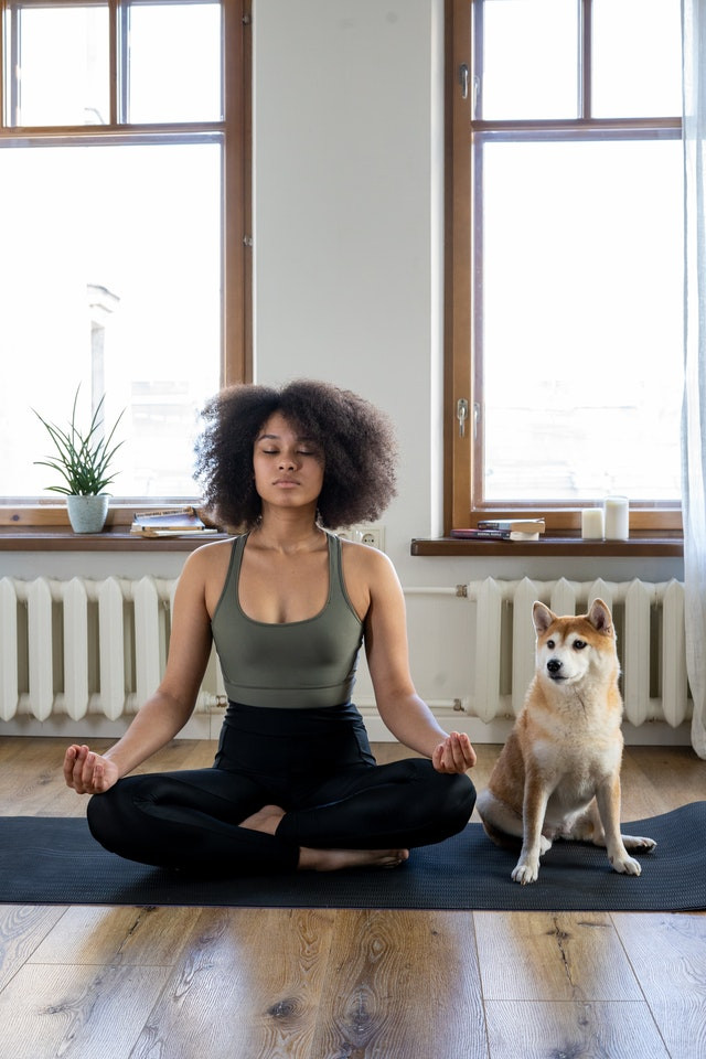Woman meditates next to her dog