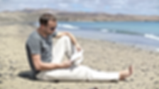 young-man-sitting-on-the-beach-and-readi