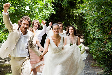 Bride, groom and guests walking along avenue of trees at outdoor wedding venue.