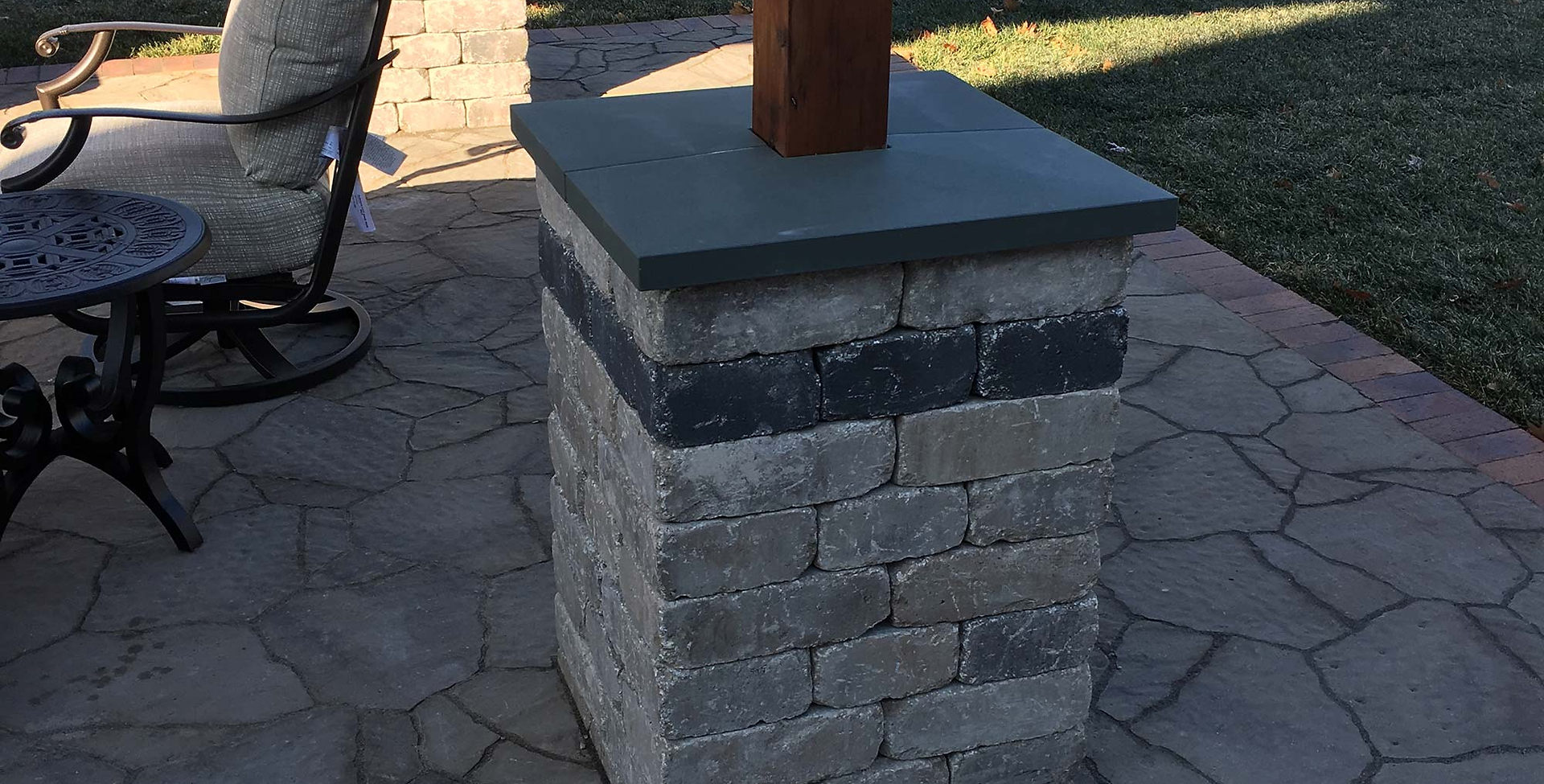 Pergola pillar with stone cap ledge.
