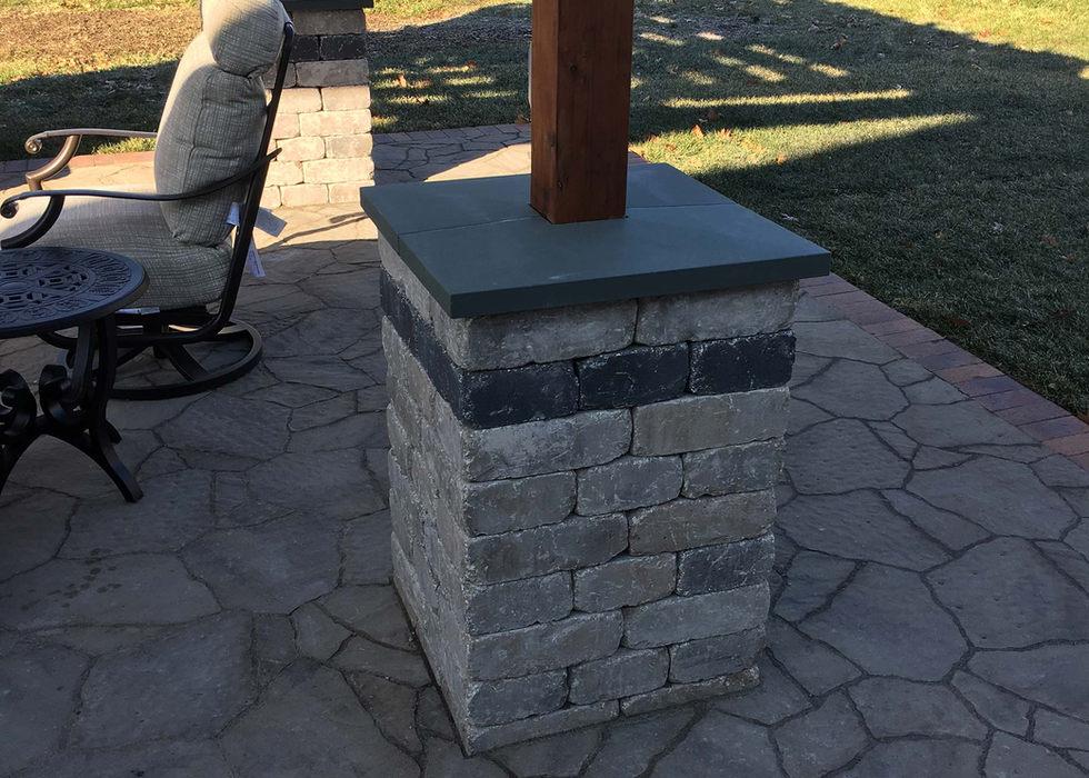 Pergola pillar with stone cap ledge.