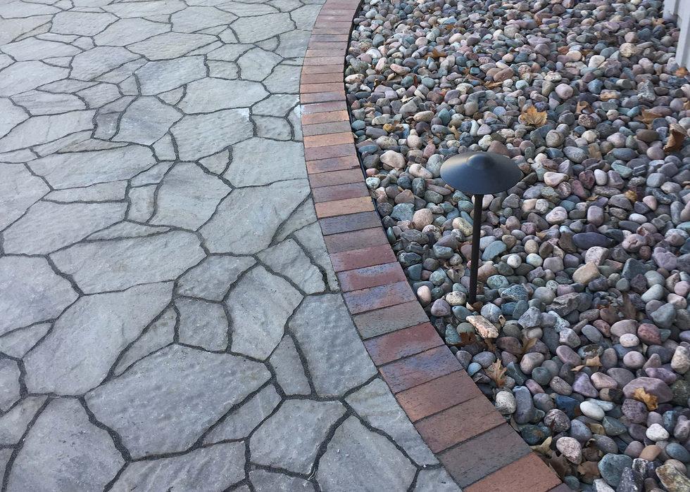 Mega arbel walkway with a brick border and lighting.