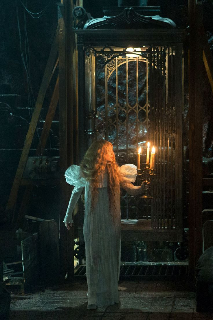 Mia Wasikowska as Edit Cushing in a white night gown holding a candelabrum in front of the cage elevator in the film Crimson Peak (2015)