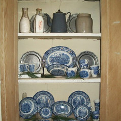 Cabinet with some of our collection of dinnerware in the Office.