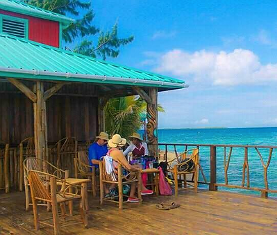 Guests eating outside the Black Pearl Restaurant & Bar on King Lewey's Island Resort, Placencia Belize