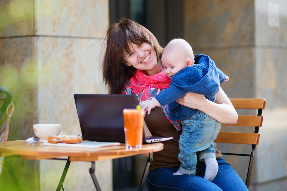 woman with child working in cafe