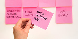 a person holding up sticky notes detailing testing a prototype