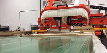 The C-West CNC machine cutting through a sheet of MDF