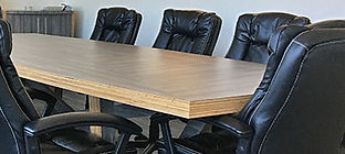 A close up of the boardroom table surrounded by meeting chairs