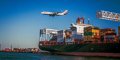 an airplane flying in the air and shipping crates stacked on a huge ship
