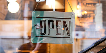 An open sign on a glass door to a retail store, reading open for business