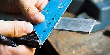a journeyman measuring a length of aluminium extrusion