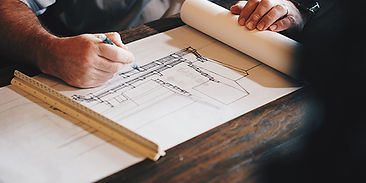 A designer or engineer drawing on draftng paper