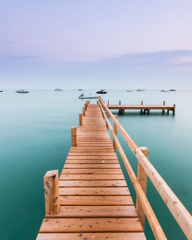 A small wooden pier heads into the dista