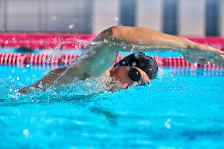 Swimmer man doing crawl swim in swimming