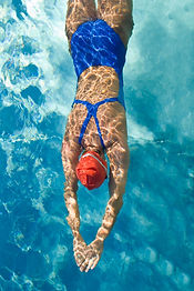 Athletic swimmer is diving in a swimming