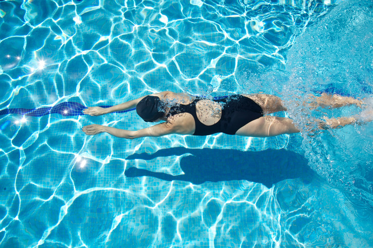 woman with swimsuit swimming on a blue w