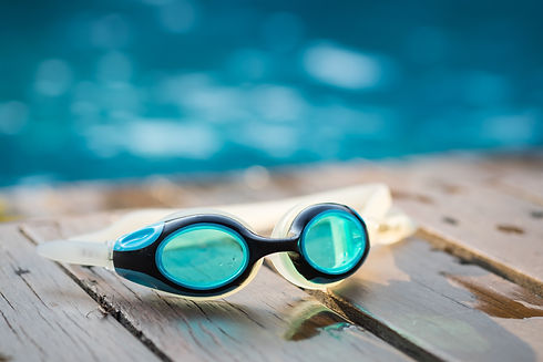 Goggles on the side of a swimming pool,