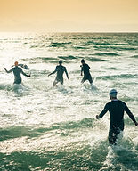 Athletic swimmers entering the water wit
