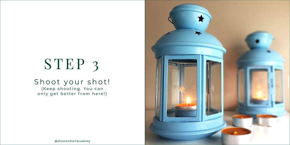 Two light blue lanterns with one in front of the other. Both have lit, orange tealight candles inside. There are 3 unlit, orange tealight candles sitting beside one of the lanterns.