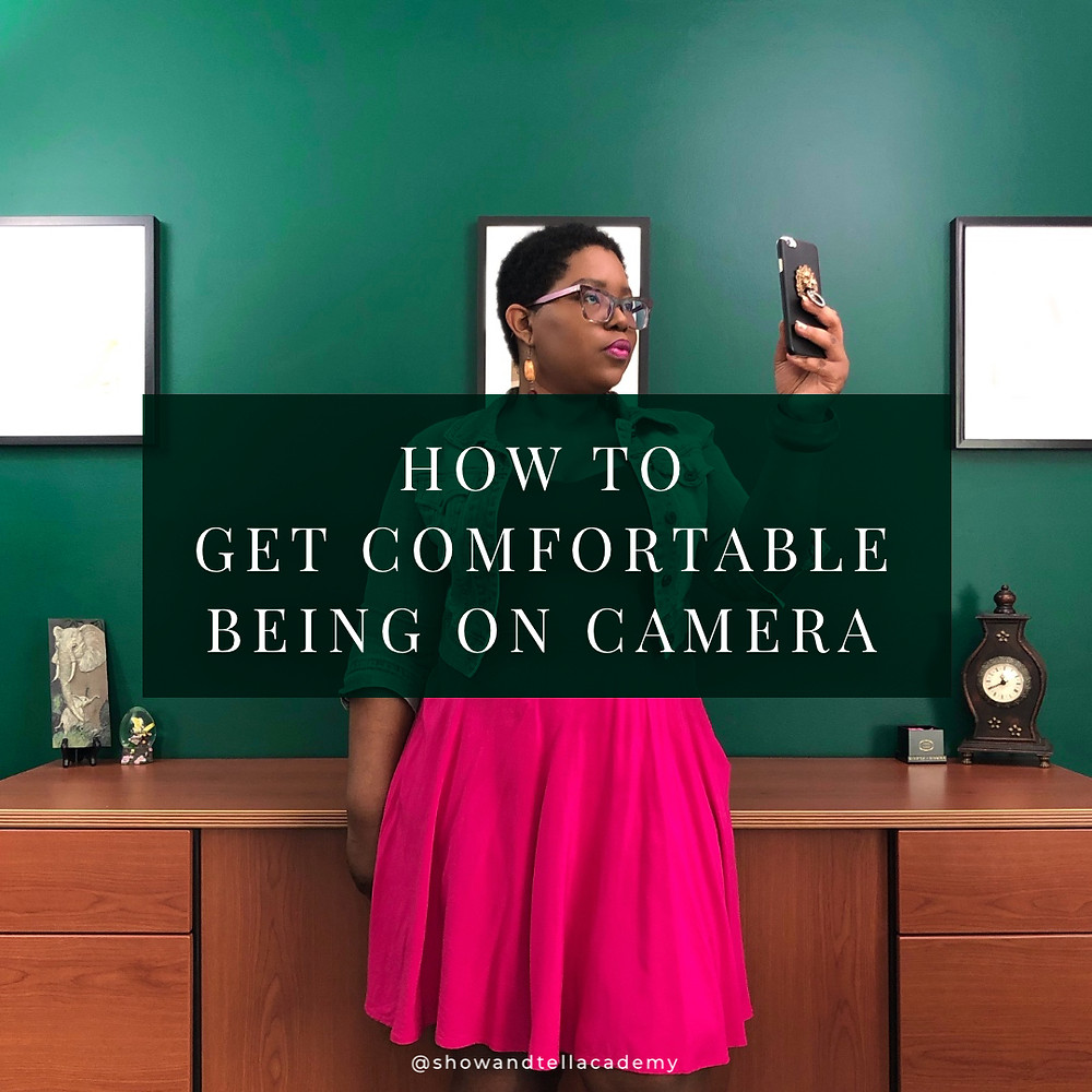 """Dominique standing against a green wall holding an iPhone as if she's taking a selfie or shooting a video. There is a dark green rectangle with the text, """"How to Get Comfortable Being on Camera""""."""