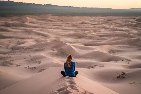 femme vue de dos, assise en tailleur, contemplant le désert