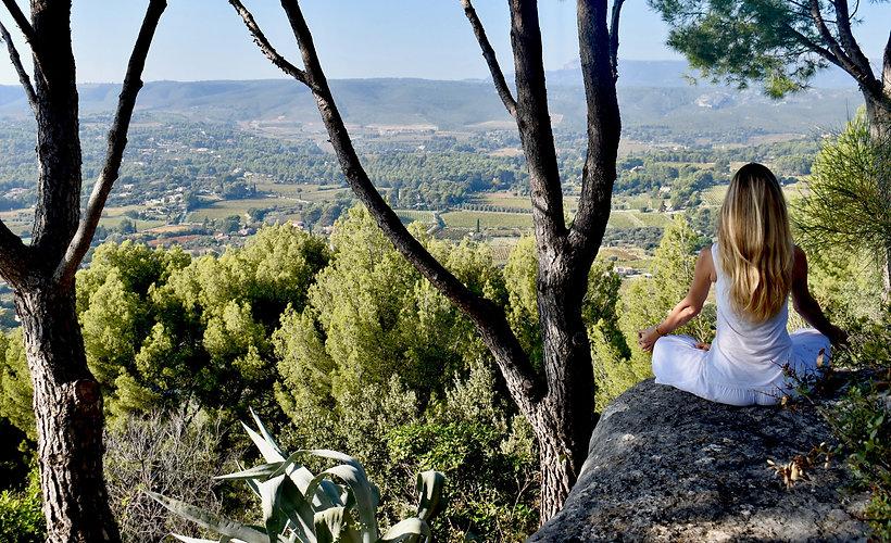 Femme de dos en tailleur devant une vallée