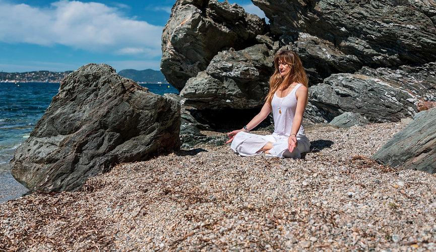 femme assise face à la mer en position de méditation